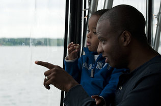 Miles Pierce, 2, secure in the arms of his father, Michael, looks out for Normie from the top deck of the boat.