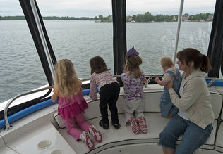 "From left, Meagan Boone, 4; Ava Szakaly, 3; Samantha Hays, 3; McKanna Hays, 10 months; and Karyn Hays look out for Normie on the first of many planned summer ""Lake Norman Monster Cruises."" On the cruises, families watch not only for Normie the Lake Norman Monster but learn about conservation and the lake-area environment. Photos by Jeff Willhelm"